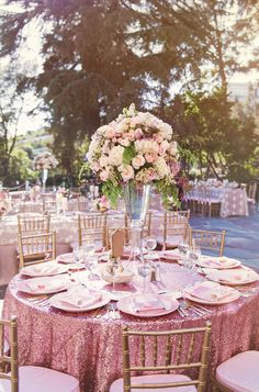 Sparkly table cloths with towering blush pink flowers for the outdoor wedding reception