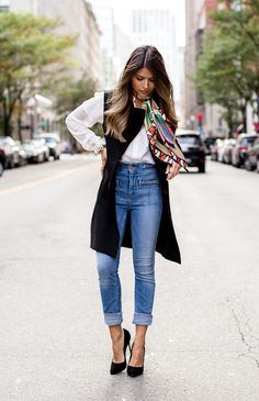 Pam Hetlinger layers the look with a long vest over a simple white shirt tucked in to high waisted jeans. She ties a multi-coloured scarf softy around her neck, and adds a pair of dark pumps.
