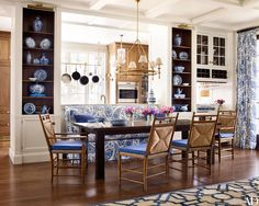 The blue-and-white porcelain displayed in the breakfast area's Christopher Peacock cabinetry inspired the house's palette; a bespoke banquette and Charles Fradin chairs cushioned with a Clarence House linen surround a Jeff Soderbergh table, while light fixtures from Circa Lighting illuminate the space.