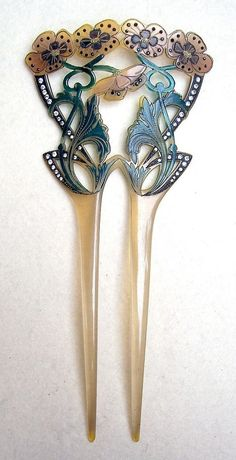 An Art Nouveau carved and painted celluloid hair comb with floral motifs.