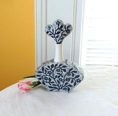 A small dark blue and white perfume bottle/decanter handmade in porcelain and hand carved with flower vines and birds. It has a beautiful classic silhouette with a lovely textural flower vine design on its surface that I hand-carved. This would make a charming gift for someone