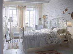 Kleine witte slaapkamer met een romantisch metalen tweepersoonsbed met nachttafeltjes en een comfortabele oorfauteuil