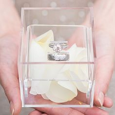 Clear acrylic wedding ring box in bride's hands