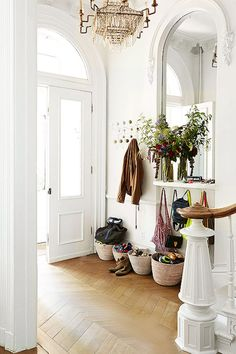 Traditional entry hall with wicker basket storage and mirror | Image via Thou Swell