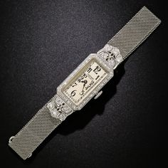 By the superior Swiss watchmaker and jeweler par excellence, Audimars Piguet, comes this exquisite early-Art Deco bracelet watch. The high-caliber timepiece is housed in an elongated rectangular case outlined by a beveled diamond-set frame. Each end is ornamented with a curvaceous diamond-set crown leading to lithe and supple platinum mesh bracelet attachment. Artful hand engraving enhances all sides of this truly exquisite 1920s vintage jewel.