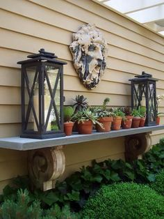 """An Outdoor Mantel to add to the side of the house or a fence.  Use 12"""" wide plank (1 1/2"""" thick) of distressed wood and support with decorative corbels (brackets).  You can add plants, lanterns, candles, topiaries or any décor."""