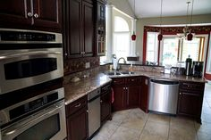 Kitchen with cherry cabinets, granite counter tops and stainless steel appliances.