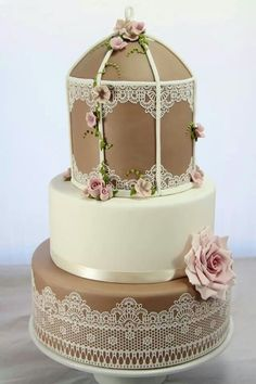 "Wedding cake in brown and beige with pink and lace accents. ""Arbor"" shaped."