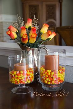 super cute and easy halloween decorations! I love the candy corn in the vases and the candles sitting right on top.