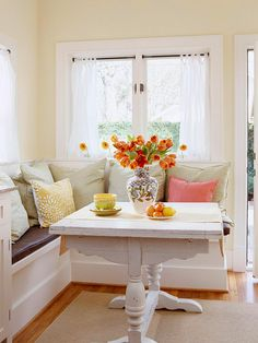 Love everything about this little dining nook - especially the table and the orange bouquet.