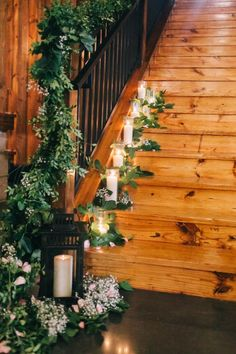Candle, lantern, and greenery wedding decor for a wedding staircase.