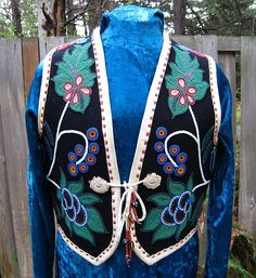 Wool vest hand beaded with Ojibwa floral designs. Fully lined. Front view. Deer antler rossettes as closure and antique trade beads. Leather trim binding all edges.