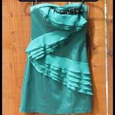 Pretty green semi-formal short dress Gorgeous deep green dress with black and dark grey crystal details on the bodice. Ruffle detail on front of dress. XOXO Dresses Prom