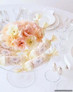 Candy Tubes  Humble supplies can take on an elegant air: Monogrammed stickers and crepe paper decorate clear plastic tubes filled with champagne-bubble candies. They're then piled into a glass compote around a smaller compote of crepe-paper flowers.