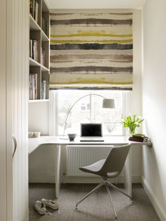 Study with built in cupboards and a mustard striped blind