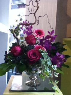 Made by me. A front facing arrangement in a gold vase containing cerise roses, cerise germini, mokara orchids, viburnum berries, ivy and twisted willow.