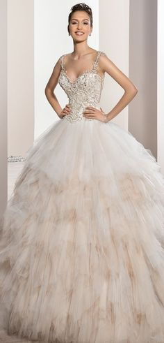 This stunning Ball gown features a richly bead embellished bodice with Sweetheart neckline and straps over sheer illusion that flows into a dramatic keyhole back accented with beading. The multi-tiered handkerchief skirt flows into Chapel train.