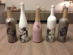 De wijnflessen eerst geverfd met gesso en daarna 2 laagjes roze & grijze verf.  Daarna beplakt met servetten en nog een laagje acrylverf eroverheen gedaan.  (Op de roze fles eerst kant geplakt en daarna pas roze geverfd).  Als laatste de flessen versierd met touw en bedeltjes.