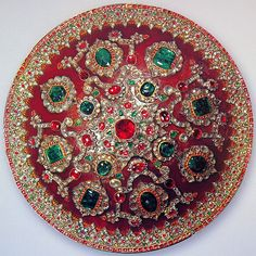 Nader Shah's shield used in India, the gems were probably added to it at a later date in his honor. Rhinoceros, 46 cm. (18 in.)  spinels, emeralds, diamonds, and rubies. The center spinel is one of the largest in the world, weighing 225 cts. The four emeralds surrounding the center spinel cover screw holes that attach straps to the back of the shield, allowing the Shah to securely hold it during battle. The largest emerald on the shield weighs 140 cts. Most of the diamonds range from 6 to 8…