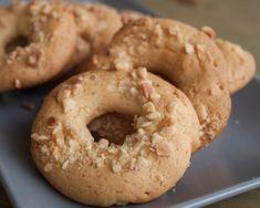 Χτυπάτε το βούτυρο με τη ζάχαρη στο μίξερ σε δυνατή ταχύτητα μέχρι να ασπρίσει.<br>Χαμηλώνετε τη ταχύτητα του μίξερ και ρίχνετε το άρωμα αμυγδάλου, την πορτοκαλάδα και λίγο-λίγο το αλεύρι. Ανακατεύετε απαλά και αφήνετε τη ζύμη για 20 λεπτά στο ψυγείο να σφίξει.<br>Πλάθετε σε ότι σχήμα θέλετε και τα τυλίγετε με τα αμύγδαλα.<br> Τα ψήνετε στο φούρνο στους 200 βαθμούς για μισή ώρα, μέχρι να ροδίσουν.<br> Αν θέλετε ρίχνετε αμύγδαλα και μέσα στη ζύμη αφού πρώτα τα καβουρδίσετε στο φούρνο. Greek Desserts, Bagel, Bread, Cookies, Food, Crack Crackers, Brot, Biscuits, Essen