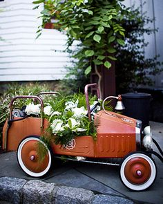 I like the idea of doing something similar to this, but instead using a vintage wagon filled with white flowers and greenery.