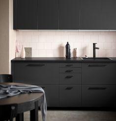 Køkken med fronter i mat antracit, som er fremstillet af 100% genanvendt affald, kombineret med sorte greb, vask og blandingsbatteri. Væggen er beklædt med pink fliser.