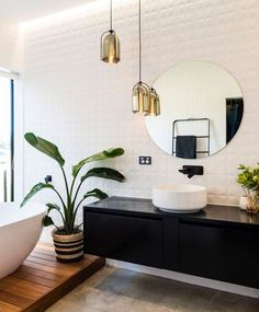 Vibrant shiny green foliage combines perfectly with the classic black and white.  The warmth of the wood combined with the organic tile floor make the room feel very relaxed and inviting.  Image from homestolovenz