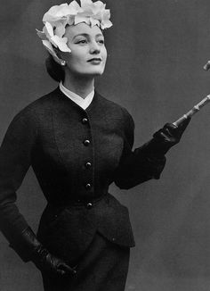 Photographed by Philippe Pottier, 1950   Dior's small wasp-waisted suit in grey wool crépe, softened by the petal hat and hint of white at the throat.