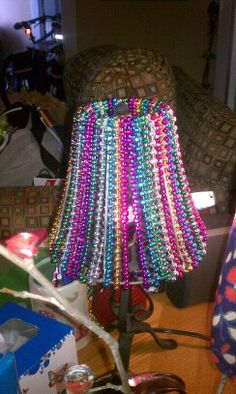 DIY lamp shade made with Mardi Gras beads! Cute cute cute: http://www.flashingblinkylights.com/mardigrasbeads-c-114_149.html