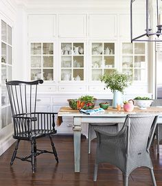 """A warm, community-oriented lifestyle was top of mind when Blazona designed her home: The 20-by-30-foot """"dream kitchen"""" has a farmhouse table that seats 12.  In this photo: Blazona's kitchen built-ins hold all her ironstone and glassware. The Windsor chair is by Ethan Allen; the wicker seats are Janus et Cie. White Dove by Benjamin Moore covers the walls.  Jann Blazona California Garden - Farmhouse Decorating and Garden Ideas - Country Living"""