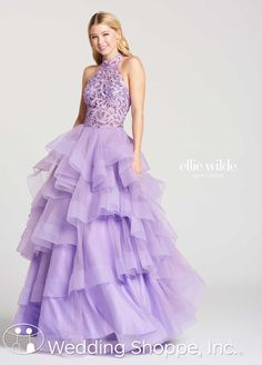 Ball gown silhouette with a high neckline, ruffled tiered skirt, and open back. Available in lavender, teal, and navy blue | Ellie Wilde Prom Dress EW118048 | The Wedding Shoppe