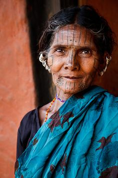 India | Portrait of a Kutia Kondh tribal woman with traditional piercings and facial tattoos, in a small village near Baliguda. Orissa.  | © Kimberley Coole