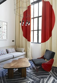 Rincón en tonos rojos coronado por #lámpara en suspensión de @vibialight. Disponible en Innova | Hotel Ministère en Paris por Agence François Champsaur