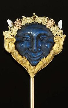 A late 19th century gold, labradorite and enamel stickpin - Modelled as the mask of Bacchus, the carved labradorite face with three colour gold beard and and grape vine crown detail and white enamel horns, circa 1890