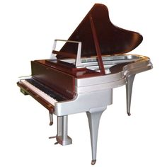 Mid Century Aluminum Grand Piano by Rippen: Netherlands 1950's :   A fantastic instrument cased in a spectacular cabinet! The Rippen aluminum bodied piano was a revolutionary design when introduced in the mid 1950's. The tensile strength of the cast aluminum cabinet allowed the profile to be much thinner, while producing a rich and full tone. The example shown has been refinished by a noted East Coast piano company in automotive lacquer and rich wood tones. Also custom installed was.....