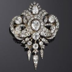 A mid 19th century diamond brooch/pendant, circa 1860 Of openwork foliate and scroll design, set throughout with old brilliant-cut diamonds and rose-cut diamond points, the principal stones in collet settings, terminating in three drops, mounted in silver and gold, diamonds approximately 15.80 carats total