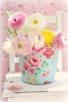 Pretty flowers in floral bucket with background of pink florals.