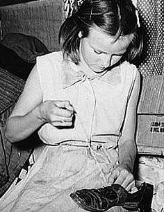 Great Depression: Daughter of white migrants repairing shoes with cotton thread. Sebastian, Texas. Photo by Russell Lee. Courtesy Library of...