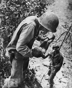 At Saipan in 1943, hundreds of Japanese civilians committed suicide rather than surrender to the Americans. As the Marines were clearing hiding Japanese from local caves, they found this infant, wedged face-down in the dirt, under a rock, nearly dead. One of the famous images of World War II, W. Eugene Smith's photo caught a rare moment of both brutality and gentleness that was unique in the annals of war photography.