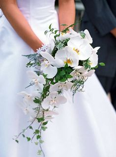 Garden style white cascade style bridal bouquet with white phalaenopsis orchids, tree fern, english ivy, and Italian ruscus.