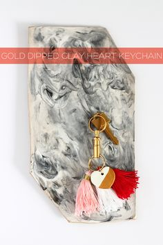 With air dry clay and gold paint, you can DIY this adorable heart key chain, perfect for Valentine's Day - especially with red, white, and pink tassels | Squirrelly Minds