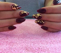 Almond nail extensions in a deep winter maroon and gold leaf