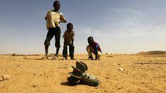 Crianças olham para projétil achado no campo de refugiados Al-Abassi, no norte de Darfur, República Centro-Africana