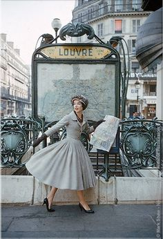 The model is at the Paris Louvre Metro Station wearing a gray Christian Dior dress. captured by legendary photographer Mark Shaw for LIFE Magazine in 1957.