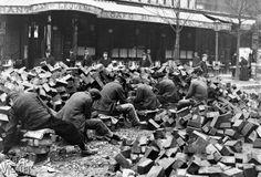 Pavage des rues de Paris. La taille des pavés de bois, vers 1920. © Jacques Boyer / Roger-Viollet