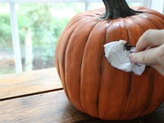 Pin for Later: A Clever Hack For Making Plastic Pumpkins Look Real  Gently wipe up and down over the paint to create the smudged, authentic look of the pumpkin.