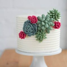 """Buttercream cake with piped buttercream succulents and roses."""