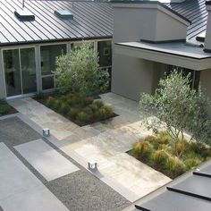simple contemporary courtyard with pale stone, gravel and block planting