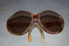 Sie interessieren sich hier für eine ausgefallene vintage Sonnenbrille  Die Sonnenbrille ist durch ihre runde Form und ihre geschwungenen Bügel ein ausgefallener Hingucker   Da es sich um ein ...