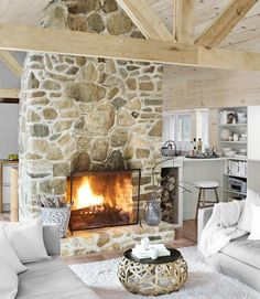Love this color monochromatic color scheme of white cream beige with the stone and rustic wood timber vaulted ceiling. White slipcovers.